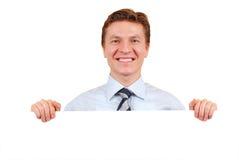 Hombre de negocios confidente que lleva a cabo a una tarjeta blanca Foto de archivo libre de regalías