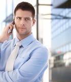 Hombre de negocios confidente usando móvil al aire libre Foto de archivo libre de regalías