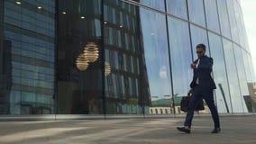 Hombre de negocios de Confindent en traje con el bolso de cuero negro que camina y que mira en los relojes en distrito financiero