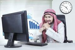 Hombre de negocios confuso con el gráfico de la disminución en oficina Imágenes de archivo libres de regalías