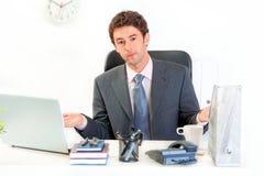 Hombre de negocios confuso que se sienta en el escritorio de oficina Fotografía de archivo libre de regalías