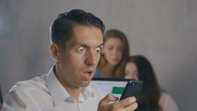 Hombre de negocios confuso que usa smartphone en la oficina Situación de choque El hombre siente repugnancia en lo que él vio en  almacen de video