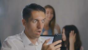 Hombre de negocios confuso que usa smartphone en la oficina Situación de choque El hombre siente repugnancia en lo que él vio en  metrajes