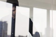 Hombre de negocios contemplativo que mira abajo en el otro lado de una pared de cristal Fotos de archivo libres de regalías