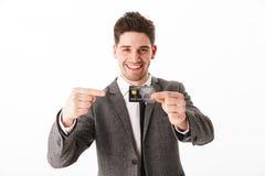 Hombre de negocios contento en la chaqueta que sostiene la tarjeta de crédito imagen de archivo libre de regalías