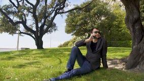 Hombre de negocios contento que habla en smartphone en el parque, sentándose en hierba cerca de árbol almacen de metraje de vídeo