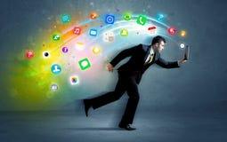 Hombre de negocios corriente con los iconos del uso del dispositivo Fotos de archivo