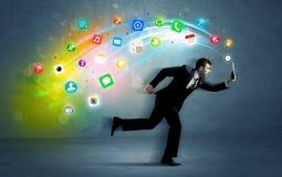 Hombre de negocios corriente con los iconos del uso del dispositivo Foto de archivo libre de regalías
