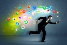 Hombre de negocios corriente con los iconos del uso del dispositivo Imagen de archivo