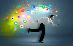 Hombre de negocios corriente con los iconos del uso del dispositivo Imagenes de archivo