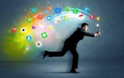 Hombre de negocios corriente con los iconos del uso del dispositivo Foto de archivo
