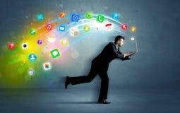 Hombre de negocios corriente con los iconos del uso del dispositivo Imágenes de archivo libres de regalías
