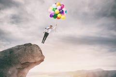 Hombre de negocios creativo que sostiene moscas coloridas de los globos del pico de una montaña fotos de archivo