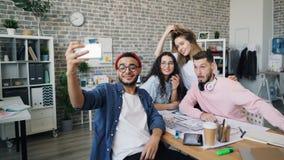 Hombre de negocios creativo que toma el selfie con el equipo del negocio en oficina moderna almacen de video