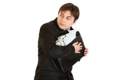 Hombre de negocios cuidadoso que abraza la cartera con el dinero Foto de archivo