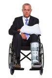 Hombre de negocios dañado en un sillón de ruedas aislado Imagenes de archivo