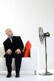 Hombre de negocios dado una sacudida eléctrica con el ventilador Fotos de archivo