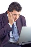 Hombre de negocios dado una sacudida eléctrica que trabaja en una computadora portátil Imágenes de archivo libres de regalías