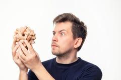 Hombre de negocios de 25 años atractivo que considera confundido el rompecabezas de madera Foto de archivo libre de regalías