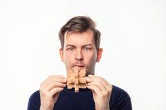 Hombre de negocios de 25 años atractivo que considera confundido el rompecabezas de madera Imagen de archivo