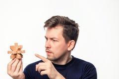 Hombre de negocios de 25 años atractivo que considera confundido el rompecabezas de madera Foto de archivo