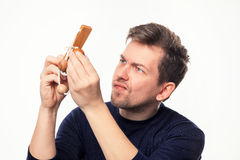 Hombre de negocios de 25 años atractivo que considera confundido el rompecabezas de madera Fotografía de archivo