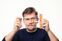 Hombre de negocios de 25 años atractivo que considera confundido el rompecabezas de madera Imagenes de archivo
