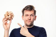 Hombre de negocios de 25 años atractivo que parece confundido con rompecabezas de madera Fotos de archivo libres de regalías
