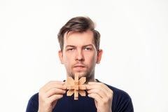 Hombre de negocios de 25 años atractivo que parece confundido con rompecabezas de madera Imagenes de archivo