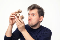 Hombre de negocios de 25 años atractivo que parece confundido con rompecabezas de madera Foto de archivo libre de regalías