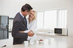 Hombre de negocios de abarcamiento de la mujer en la cocina Imagen de archivo