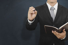 Hombre de negocios de Asia que sostiene la pluma del bookand y que piensa en la pared en blanco para Imagen de archivo