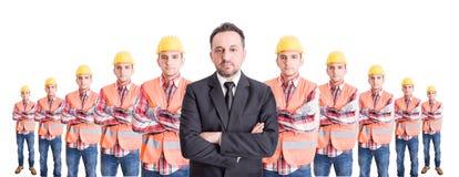 Hombre de negocios de Confindent y un equipo de trabajadores de construcción Fotos de archivo libres de regalías