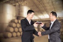 Hombre de negocios de dos asiáticos que sostiene un vidrio de vino y de apretón de manos Fotos de archivo