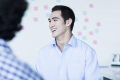 Hombre de negocios de dos jóvenes que ríe y que habla en la oficina Imagen de archivo libre de regalías