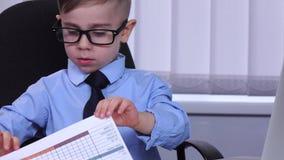 Hombre de negocios de dos niños pequeños que mira el ordenador portátil y que está a favor del diagrama almacen de video