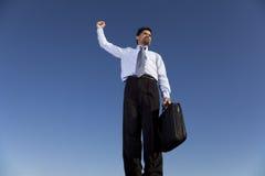 Hombre de negocios de gran alcance que sostiene una cartera Foto de archivo libre de regalías