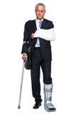 Hombre de negocios de Injred en las muletas en blanco Foto de archivo libre de regalías