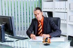 Hombre de negocios de la burocracia con el sello que parece enojado Foto de archivo