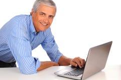 Hombre de negocios de la Edad Media en el escritorio con la computadora portátil Imagenes de archivo