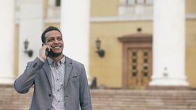 Hombre de negocios de la raza mixta que llama el teléfono móvil al aire libre