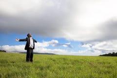 Hombre de negocios de la relajación que se coloca en el campo verde Fotografía de archivo