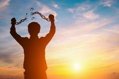 Hombre de negocios de la silueta con las cadenas quebradas en puesta del sol foto de archivo