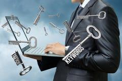 Hombre de negocios de los diales de las palabras claves en el ordenador Imagen de archivo