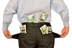 Hombre de negocios de los hombres que muestra los bolsillos vacíos que ocultan detrás de tacos del dinero Fotografía de archivo libre de regalías