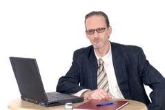 Hombre de negocios de mirada pensativo que trabaja en la computadora portátil Foto de archivo libre de regalías