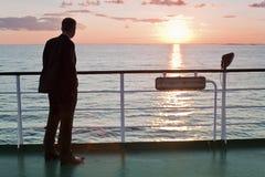 Hombre de negocios de pensamiento y puesta del sol roja en un transbordador Foto de archivo