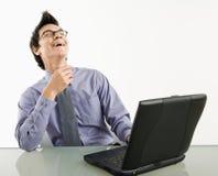 Hombre de negocios de risa en la computadora portátil. foto de archivo