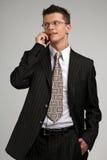 Hombre de negocios de Smilling que habla en un teléfono Fotos de archivo libres de regalías
