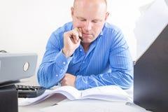 Hombre de negocios de trabajo duro en la oficina Fotografía de archivo libre de regalías